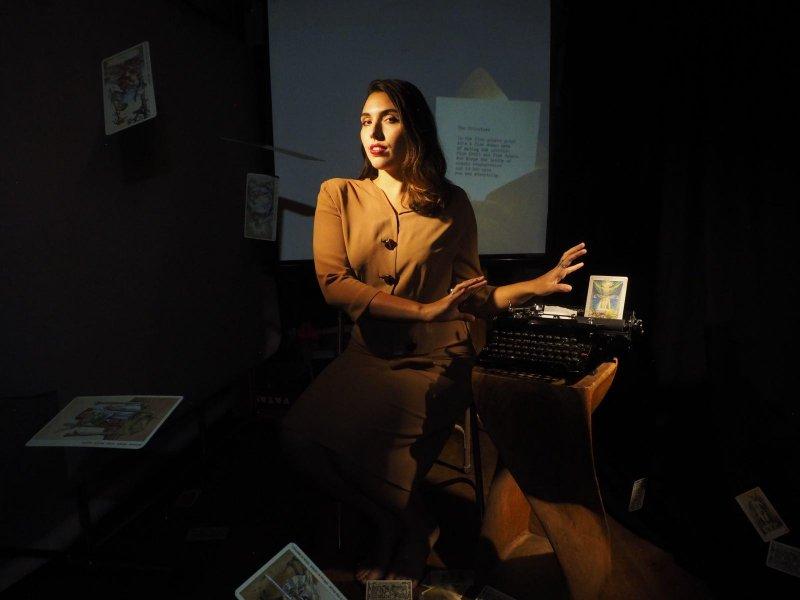 dark haired women reading taror cards with vintage typwriter